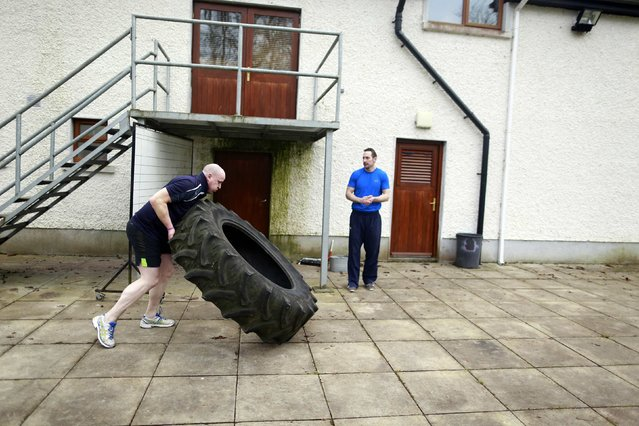 Fr Pierre Pepper turns over a tractor tyre during training at the Aspire gymnasium in the town of Clara County Offaly February 12, 2015. (Photo by Cathal McNaughton/Reuters)