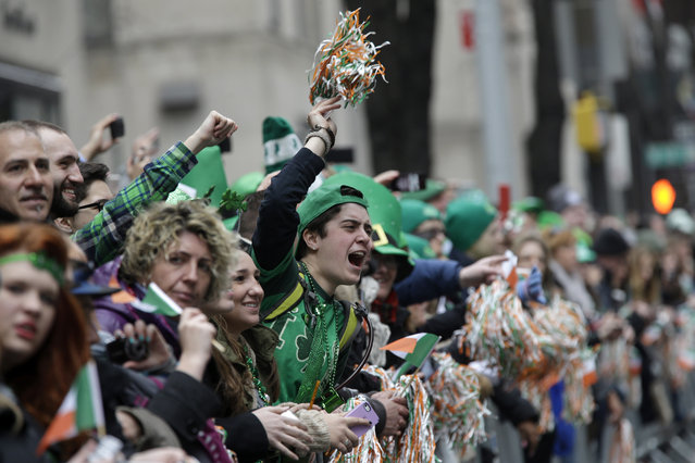 Melissa Soucy, center, of Morristown, N.J. waves at the participants marching up 5th Ave during the St. Patrick's Day Parade, Tuesday, March 17, 2015, in New York. (Photo by Mary Altaffer/AP Photo)