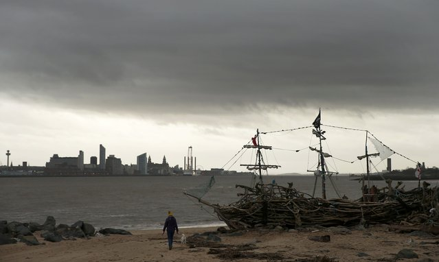A women walks her dog under a dark sky past the Black Pearl driftwood pirate ship on New Brighton beach near Wallasey in Britain January 26, 2016. (Photo by Phil Noble/Reuters)