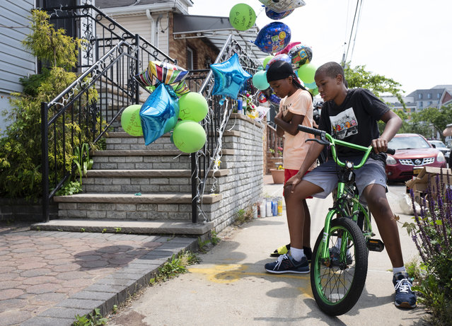 """Boys stop to look at a memorial for ten-year-old Justin Wallace, Tuesday, June 8, 2021 in the Far Rockaway neighborhood of New York. The boy was killed and his 29-year-old uncle was wounded as they entered the home, Saturday, June 5. Mayor Bill de Blasio called Justin's death """"a profound injustice"""" on Twitter. """"His killer will be brought to justice"""", he said. (Photo by Mark Lennihan/AP Photo)"""