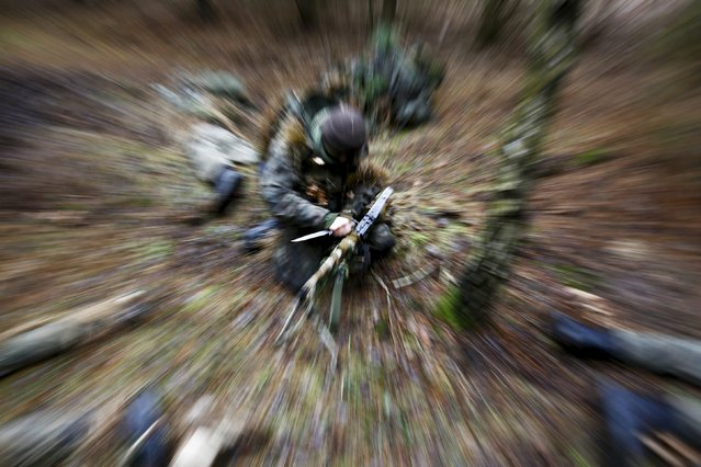 Damian Trynkiewicz installs his weapon during territorial defence training organised by SJS Strzelec (Shooters Association), paramilitary group in the forest near Minsk Mazowiecki, eastern Poland March 14, 2014. (Photo by Kacper Pempel/Reuters)