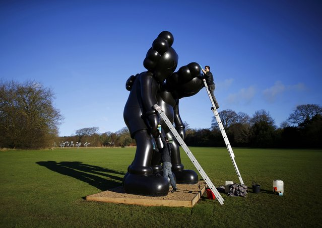 """Workers clean a sculpture entitled """"Along The Way"""" by American artist Kaws at the Yorkshire Sculpture Park in Wakefield, Britain February 3, 2016. (Photo by Darren Staples/Reuters)"""