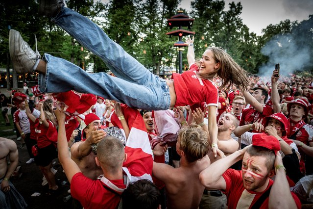 Danish football fans react to their team's first goal as they watch the UEFA EURO 2020 semi-final football match between England and Denmark on the giant screen in Tivoli in Copenhagen, on July 7, 2021. (Photo by Mads Claus Rasmussen/Ritzau Scanpix via AFP Photo)