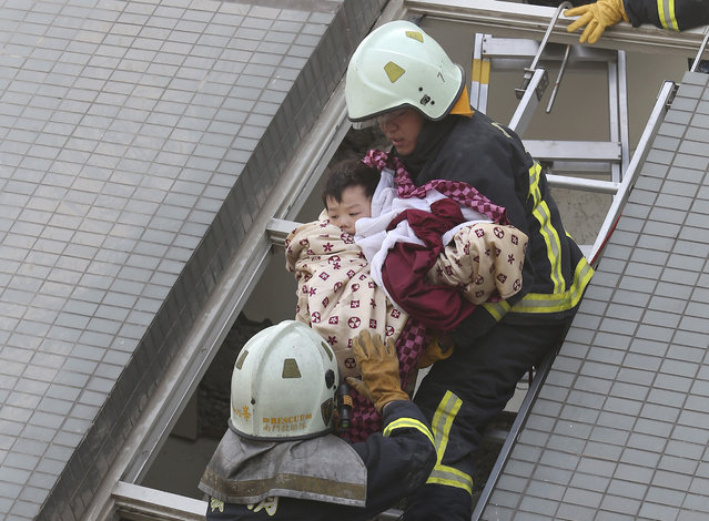 A child is rescued from a toppled building after a 6.4-magnitude earthquake in Tainan, Taiwan, Saturday, February 6, 2016. (Photo by AP Photo)