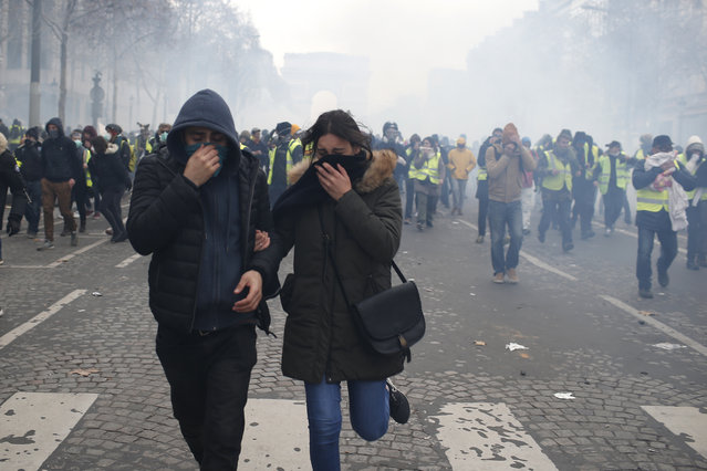 Demonstrators run away amid tear gas on the Champs-Elysees avenue Saturday, December 8, 2018 in Paris. (Photo by Rafael Yaghobzadeh/AP Photo)