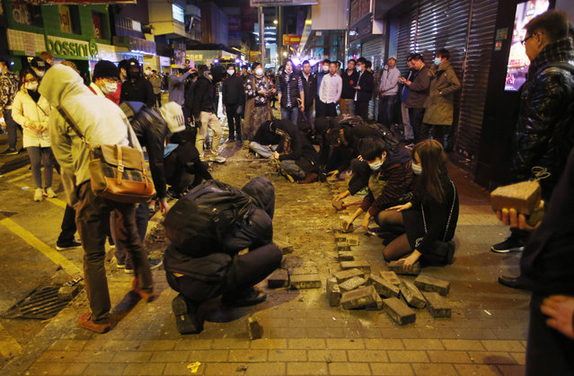 Protesters collect bricks from a pathway during clashes with police in Mong Kok district of Hong Kong, Tuesday, February 9, 2016. (Photo by Kin Cheung/AP Photo)