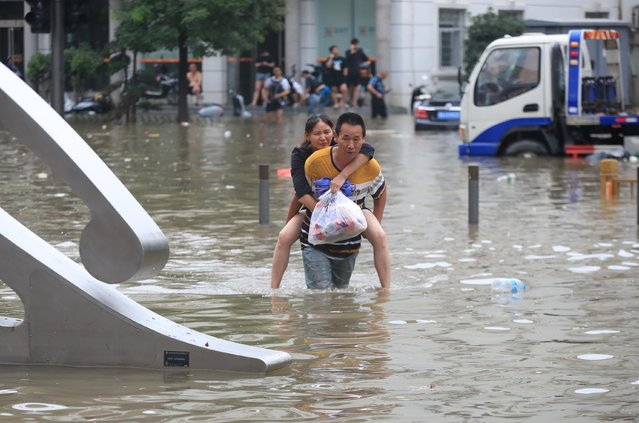 A man carrying a woman wades through a flooded road following heavy rainfall in Zhengzhou, Henan province, July 21, 2021. At least 25 people have died in China's flood-stricken central province of Henan, a dozen of them in a subway line in its capital that was drenched by what weather officials called the heaviest rains for 1,000 years. (Photo by China Daily via Reuters)