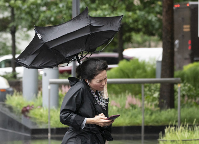 A woman's umbrella is flipped inside out as she walks on a rainy and windy New York street, Friday, July 9, 2021. Fast-moving Tropical Storm Elsa hit the New York City region with torrential rains and high winds as it churned up the East Coast. (Photo by Mark Lennihan/AP Photo)