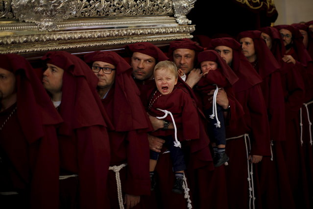 """The 18-month-old fraternal twins, Nacho Guirado (L) and Asier cry as they are carried by their father Ignacio (L) and their uncle Jose Carlos, who are twins, while lifting a float bearing the statue of the Virgin inside a church as they take part as penitents in the """"Salud"""" brotherhood in a Palm Sunday procession at the start of Holy Week in Malaga, southern Spain, March 29, 2015. (Photo by Jon Nazca/Reuters)"""