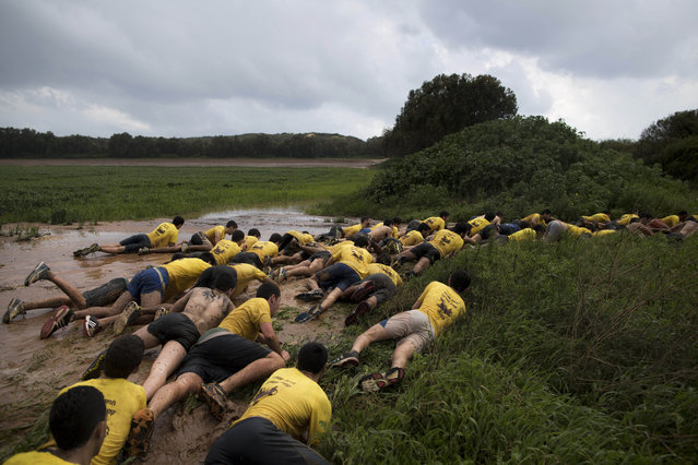 In this Friday, February 13, 2015 photo, Israeli high-school seniors preparing to join the Israeli military later this year crawl out of mud up to a grassy embankment during an exercise at a privately run training camp for military combat fitness near Yakum, central Israel. (Photo by Oded Balilty/AP Photo)