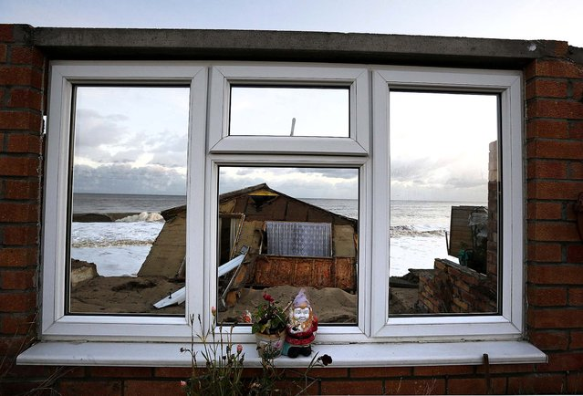 A garden gnome sits on the window of a house that fell into the sea during a storm surge in Hemsby, England, on December 6, 2013. (Photo by Darren Staples/Reuters)