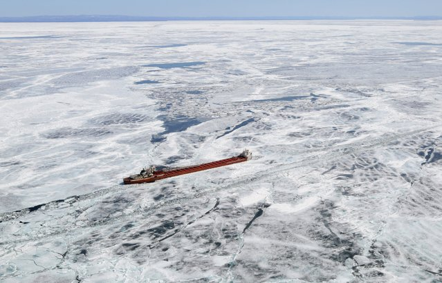 A freighter trapped in ice is shown in this aerial photo near Whitefish Bay on Lake Superior northwest of Sault Ste. Marie, Ontario April 7, 2015. The biggest ice cover on the Great Lakes in decades is backing up shipments of everything from Canadian grain to U.S. iron and steel in one of North America's most important economic regions. (Photo by Kenneth Armstrong/Reuters)