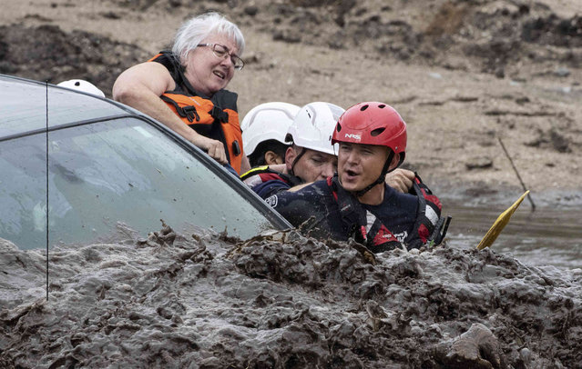 A woman climbs out of a Nissan pickup truck as Golder Ranch firefighters position themselves for a water rescue in the Cañada del Oro Wash north of Tucson, Ariz., on Tuesday, August 10, 2021. Firefighters rescued three people from one of two vehicles in the wash, swollen with runoff after an early-morning downpour dumped nearly two-inches upstream. (Photo by Rick Wiley/Arizona Daily Star via AP Photo)
