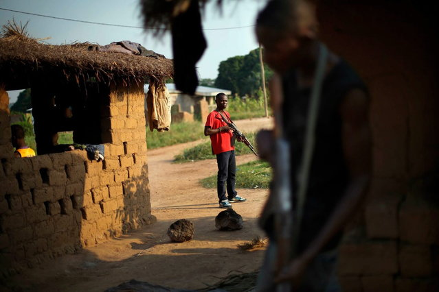 A former FARCA (Central African Republic Forces) soldier linked to Anti-Balaka Christian militiamen guards their camp in the Boeing neighborhood of the Central African Republic's capital Bangui Sunday December 15, 2013. (Photo by Jerome Delay/AP Photo)