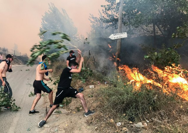 People attempt to put out a fire in the mountainous Tizi Ouzou province, east of Algiers, Algeria on August 10, 2021. (Photo by Abdelaziz Boumzar/Reuters)