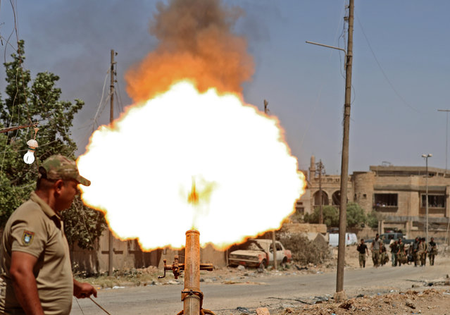 Members of the Iraqi forces fire mortar shells during battles in western Mosul's Zanjili neighbourhoodm, as government forces advance in the area during their ongoing battle against Islamic State (IS) group fighters on May 31, 2017. (Photo by Karim Sahib/AFP Photo)