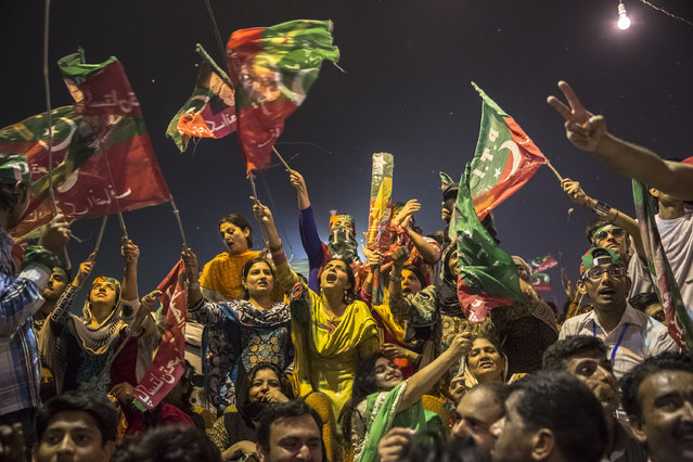 Supporters wave flags and cheer prior to the arrival of Imran Khan, chairman of the Pakistan Tehrik e Insaf (PTI) party, during an election campaign rally on May 06, 2013 in Multan, Pakistan. (Photo by Daniel Berehulak/Getty Images)