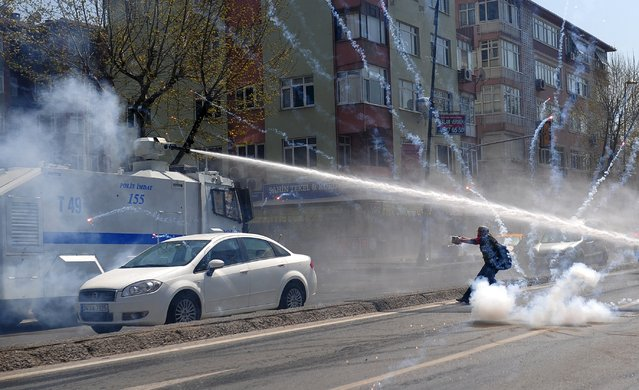 Police use tear gas and water cannons against leftist protesters, as one of them shoots firecrackers at an armoured police vehicle, during clashes after the office of Istanbul's Governor banned the concert of left-wing band Grup Yorum in Istanbul April 12, 2015. (Photo by Yagiz Karahan/Reuters)