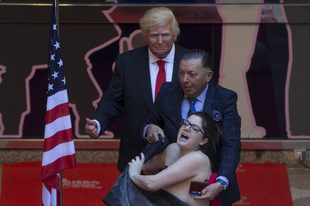 A woman makes a semi-naked protest during the inauguration of a figure of U.S. President-elect Donald Trump at the Wax museum in Madrid, Spain, Tuesday, January 17, 2017. (Photo by Paul White/AP Photo)