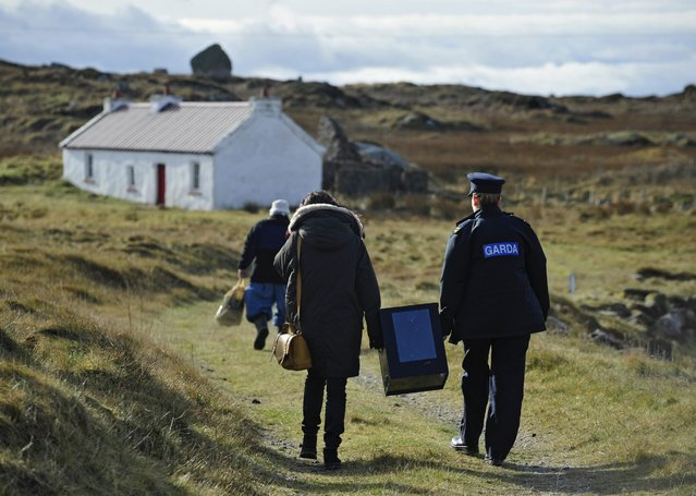 Magella Harkin and Garda Margaret Byrne carry a ballot box from a boat to a polling station on the Island of Innishfree, where two people voted, off the Coast of Donegal in Ireland, 25 February 2016. Over two thousand people live on islands off the coast of Ireland who vote early in the Irish General Election. The rest of the country go to the polls on 26 February 2016. (Photo by Aidan Crawley/EPA)