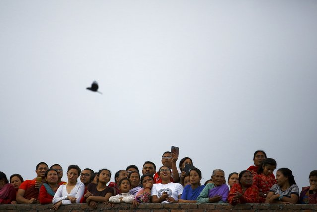 Devotees observe the chariot festival of Rato Machhindranath from the roof of a house at Bungamati in Lalitpur April 22, 2015. (Photo by Navesh Chitrakar/Reuters)