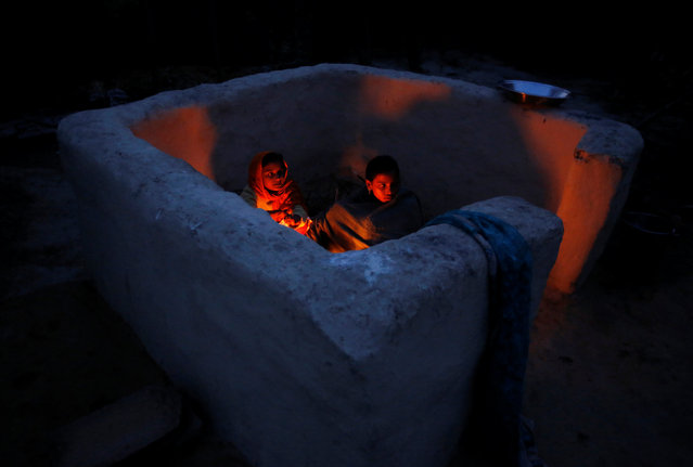 Children of a snake charmer prepare dinner outside their home in Jogi Dera (snake charmers settlement), in the village of Baghpur, in the central state of Uttar Pradesh, India January 16, 2017. An ancient tribe of snake charmers, known as Saperas, have thrived over the generations by catching venomous snakes and making them dance to their music. Snakes are revered by Hindus in India and snake charmers are considered the followers of Lord Shiva, the blue-skinned Hindu god who is usually portrayed wearing a king cobra around his neck. Snake charmers were once a regular fixture at Indian bazaars and festivals, mesmerising crowds of onlookers with their ability to control some of the world's most venomous creatures. They would often be the main source of medicines if someone suffered from a snake bite. The snake charmers of Jogi Dera say their centuries-old tradition is slowly dying out as authorities seek to enforce wildlife protection laws, and after an outright ban on the practice in 1991. (Photo by Adnan Abidi/Reuters)