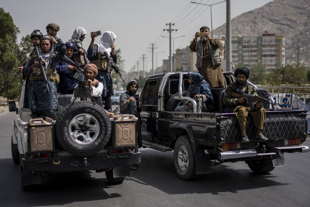 Taliban fighters escort women's march in support of the Taliban government outside Kabul University, Afghanistan, on Saturday, September 11, 2021. (Photo by Bernat Armangue/AP Photo)