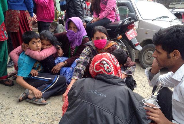 Nepalese people huddle together outside the Medicare Hospital in Kathmandu, Nepal, Saturday, April 25, 2015. (Photo by Niranjan Shrestha/AP Photo)