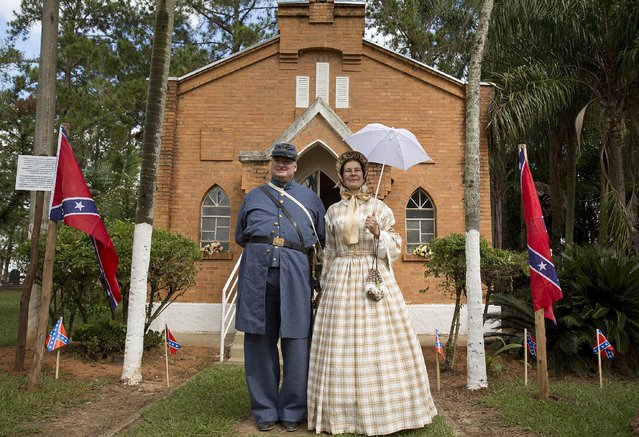 Descendants of American Southerners Philip Logan and his wife Eloiza Logan, pose for pictures during a party to celebrate the 150th anniversary of the end of the American Civil War in Santa Barbara d'Oeste, Brazil, Sunday, April 26, 2015. Thousands turn out every year, including many of those who trace their ancestry back to the dozens of families who, enticed by the Brazilian government's offers of land grants, settled here from 1865 to around 1875. (Photo by Andre Penner/AP Photo)