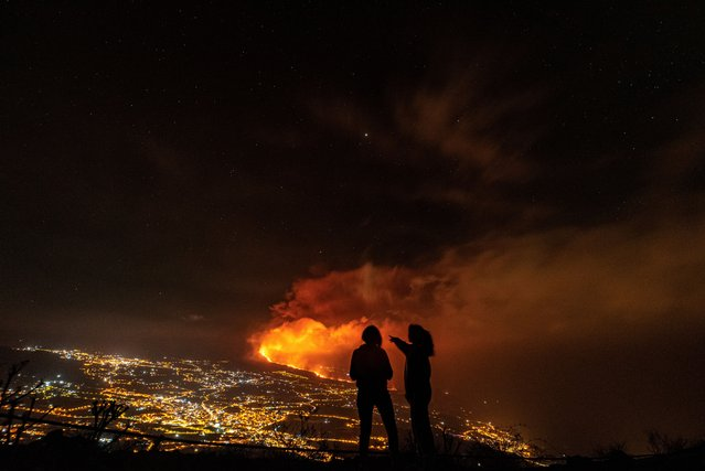 Two women look at the Cumbre Vieja volcanic eruption from the distance in Los Llanos de Ariadne in La Palma, Canary Islands, Spain, late 05 October 2021 (issued 06 October 2021). The main cone of the La Palma volcano suffered a partial collapse of its structure 03 October, while effusive activity has increased after 15 days of its beginning. According to experts the volcano is far from ending its volcanic activity. (Photo by Miguel Calero/EPA/EFE)