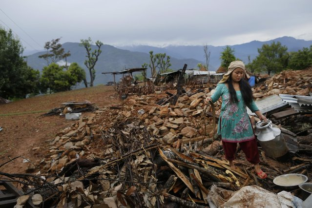 A woman recovers cooking pots from her collapsed home destroyed village of Paslang near the epicenter of Saturday's massive earthquake in the Gorkha District of Nepal, Tuesday, April 28, 2015. (Photo by Wally Santana/AP Photo)