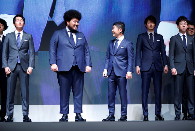 Yusaku Maezawa (3rd R), the chief executive of Zozo, which operates Japan's popular fashion shopping site Zozotown and is officially called Start Today Co, looks at his employee who wears a made-to-measure suit using a skintight bodysuit which helps customers upload their measurements online at an event launching the debut of its formal apparel items, in Tokyo, Japan, July 3, 2018. (Photo by Kim Kyung-Hoon/Reuters)