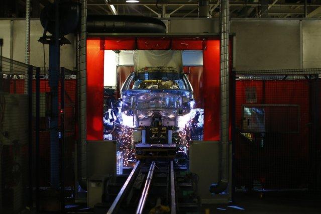 Robots work on the construction of a Peugeot 208 car at the PSA Peugeot Citroen plant in Poissy, near Paris, France, April 29, 2015. (Photo by Benoit Tessier/Reuters)