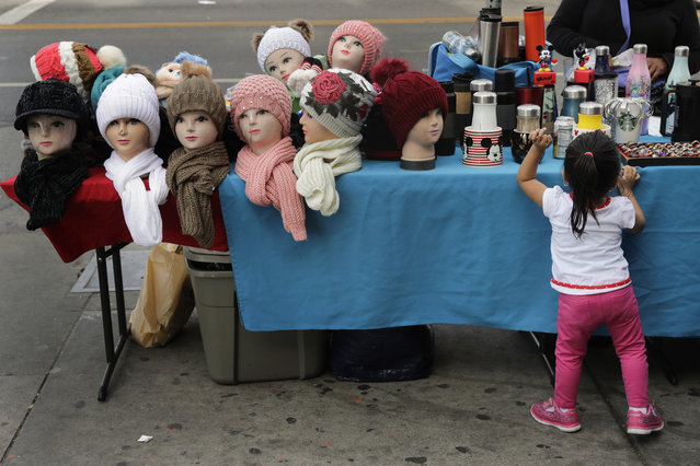 Mannequin heads with beanies are placed on a table as a young girl looks at goods for sale on a sidewalk Tuesday, November 27, 2018, in Los Angeles. They seem to be everywhere on the streets of Los Angeles – pushcarts and tables filled with everything from hot dogs and tamales to toys and tools. Such sales are illegal, although the law is rarely enforced. Now, after a decade of debate and compromise, the Los Angeles City Council will consider an ordinance Wednesday that would grant permits to sidewalk vendors. (Photo by Jae C. Hong/AP Photo)