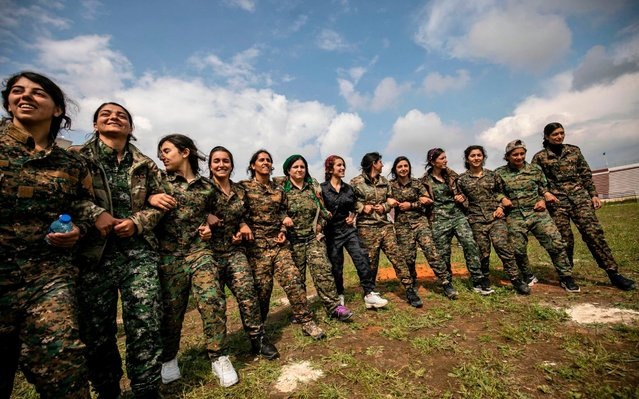 Fighters from the Kurdish Women's Protection units (YPJ)perform a traditional dance as they participate in a military parade on March 27, 2019, celebrating the total elimination of the Islamic State (IS) group's last bastion in eastern Syria, in the northwestern city of Hasakah, in the province of the same name. (Photo by Delil Souleiman/AFP Photo)