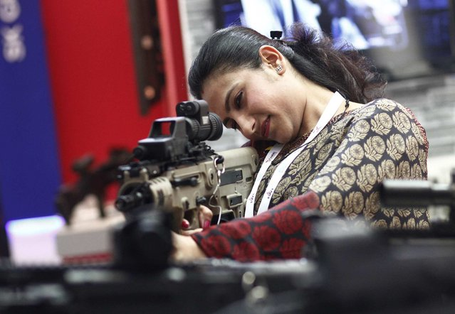 A visitor holds an Israeli-made rifle during the 8th International Land and Naval Defense system exhibition, in New Delhi, India, on February 6, 2014. (Photo by Anindito Mukherjee/Reuters)