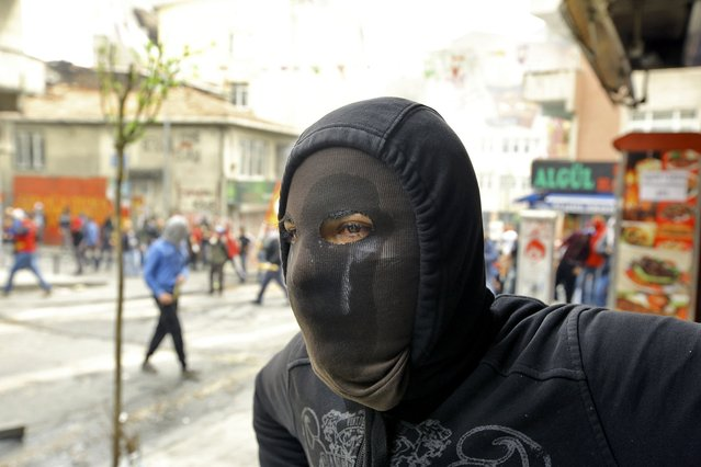 A protester looks on during clashes with police in Okmeydani neighborhood in Istanbul, Turkey, May 1, 2015. (Photo by Huseyin Aldemir/Reuters)