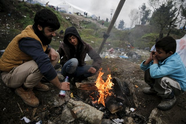 Migrants warm themselves next to a bonfire at a makeshift camp at the Greek-Macedonian border, near the village of Idomeni, Greece March 15, 2016. (Photo by Alkis Konstantinidis/Reuters)