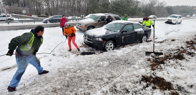 Priscilla Hernandez , background in red, watches as a tow crew pulls her vehicle from the median on Hwy 70 near I-540 Thursday, February 13, 2014, in Raleigh, N.C., the day after she left it in a winter storm. The Triangle and the state were hit by a serious winter storm Wednesday, leaving hundreds of cars stuck or stranded on and along the roadways. (Photo by Chuck Liddy/AP Photo/The News & Observer)