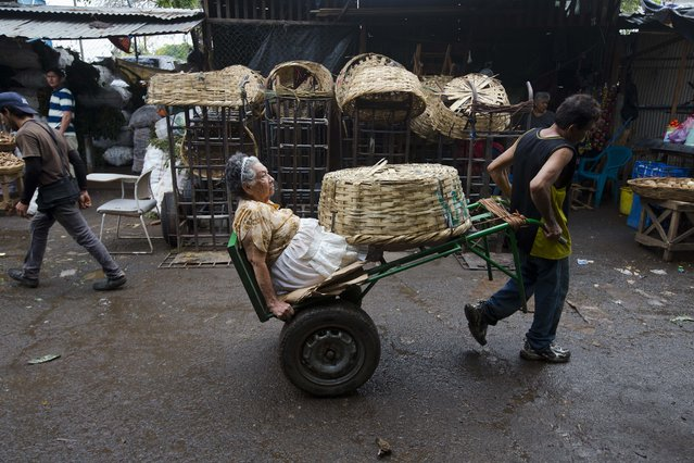 "Vendor Carmen Diaz, 84, is pulled by a market porter as she makes her way home at the end of her work day in the Oriental Market in Managua, Nicaragua, late Thursday, April 30, 2015. Known as ""Chanita"", Diaz has worked since she was 8-years-old at the market, where she sells a hodgepodge of household items that include small piggy banks, coat hooks and liquid cleaners. (Photo by Esteban Felix/AP Photo)"