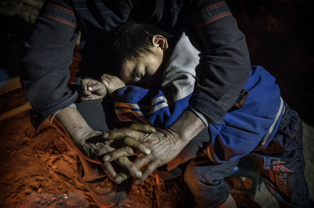 """Grandfather Luo Yingtao, 64, holds his sleeping grandson """"left behind"""" child Luo Lie, 5, as they stay warm next to a fire at the family house on December 17, 2016 in Anshun, China. (Photo by Kevin Frayer/Getty Images)"""