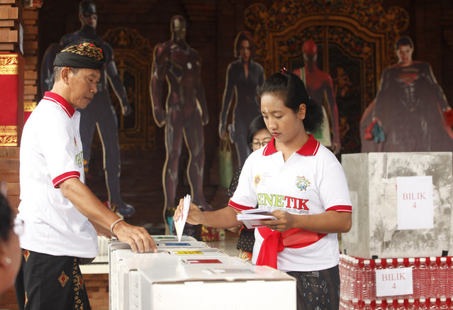 A woman casts her ballot at a polling station during election in Bali, Indonesia on Wednesday, April 17, 2019. Voting is underway in Indonesia's presidential and legislative elections after a campaign that that pitted the moderate incumbent against an ultra-nationalist former general. (Photo by Firdia Lisnawati/AP Photo)