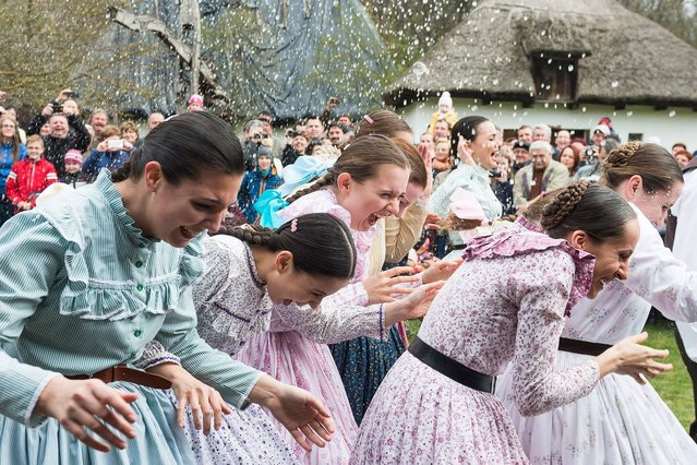 Members of Nyirseg Dance Group wearing folk costumes run away from young men who try to pour water on them from buckets, as they perform an Easter folk tradition in the Sosto Village Museum in Nyiregyhaza, Hungary on March 28, 2016. (Photo by Attila Balazs/AP Photo)