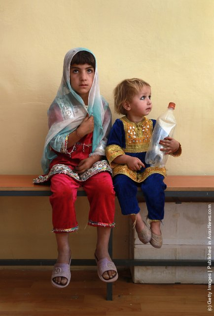 Afghan children wait as their mothers receive treatment at a USAID-funded health center