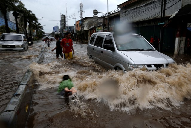 A child dives as cars wade through floodwaters in a flood-hit area at the Mangga Dua business district in Jakarta, Indonesia February 21, 2017. (Photo by Reuters/Beawiharta)