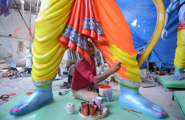 An Indian artist puts the final touches to statues of the Hindu God Lord Ram ahead of the Sri Rama Navami Festival at a workshop in Hyderabad on April 13, 2016. (Photo by Noah Seelam/AFP Photo)