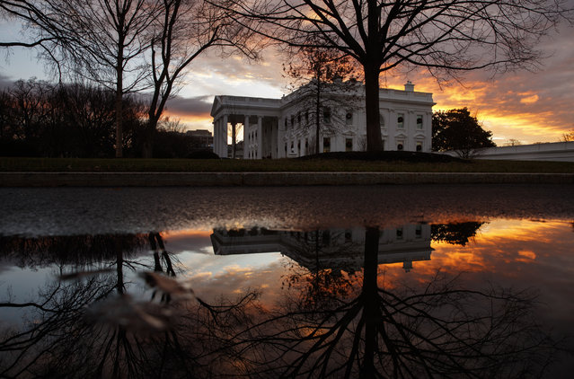The sun rises behind the White House in Washington, Saturday, December 22, 2018. Hundreds of thousands of federal workers faced a partial government shutdown early Saturday after Democrats refused to meet President Donald Trump's demands for $5 billion to start erecting a border wall with Mexico. Overall, more than 800,000 federal employees would see their jobs disrupted, including more than half who would be forced to continue working without pay. (Photo by Carolyn Kaster/AP Photo)