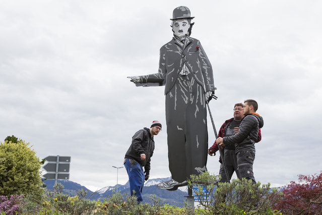 """A 3 meter high statue of the actor Charlie Chaplin is set up to  show the way to the Manoir de Ban on the eve of the opening of the museum """"Chaplin's World by Grevin"""" in Corsier-Sur- Vevey, Switzerland, Friday, April 15, 2016. Chaplin's World, a museum on English comic actor, filmmaker, and composer Charlie Chaplin, is set in a  park of lush trees, it occupy the mansion where Chaplin lived his last 25 years. (Photo by Vincent Vannay/Keystone via AP Photo)"""