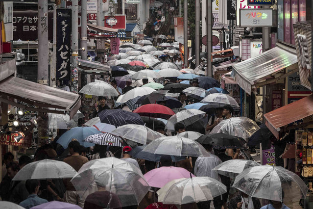 Shoppers with umbrellas walk along the Takeshita Street Friday, June 7, 2019, in the Harajuku district of Tokyo. Harajuku is one of the most popular shopping neighborhoods in Tokyo. (Photo by Jae C. Hong/AP Photo)