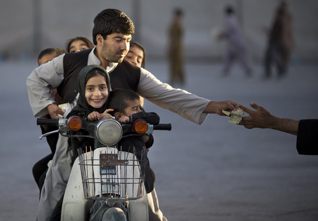 In this Friday, November 1, 2013 file photo, an Afghan man with his five children on his motorbike pays money to enter a park in Kandahar, southern Afghanistan. (Photo by Anja Niedringhaus/AP Photo)